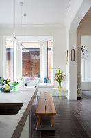 Wooden bench at kitchen island in open-plan interior with bay window
