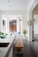 Holzbank an der Kücheninsel im offenen Wohnraum mit Erkerfenster