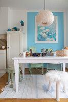 Weißer Tisch und Hocker vor hellblauer Wand in offener Küche