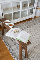 Book and teacups on wooden bench next to white glass-fronted cabinet