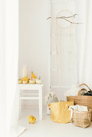 Pale, modern, autumn arrangement of pumpkins, ladder on wall, dreamcatcher and baskets