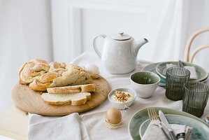 Sliced plaited yeast loaf on set table