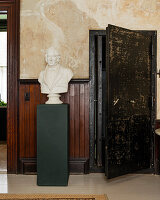 Plaster bust on green plinth in room with wooden wall panelling and large walk-in safe