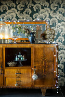 Festive decorations on old sideboard against vintage-style wallpaper