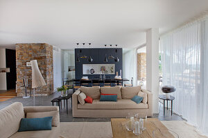 Sandfarbene Polstergarnitur in offenem Wohnraum, im Hintergrund Essbereich und Raumteiler