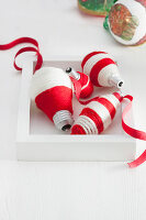 Christmas decorations made from light bulbs wrapped in yarn