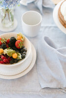 Bowl of berries and cape gooseberries on table with linen tablecloth