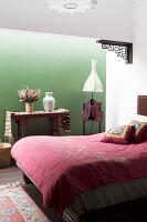 Doppelbett im Schlafzimmer mit grüner Wand
