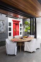 Überdachte Terrasse mit Rattantisch, Hussenstühlen, vertikaler Bepflanung und roter, chinesischer Tür