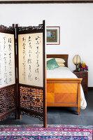 Paravent mit chinesischen Schriftzeichen vor Vintage Doppelbett aus Holz