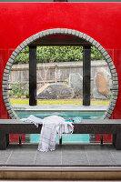 Steinbank mit Badetuch und Taucherbrille vor rundem Ausschnitt, mit Blick auf das Schwimmbecken