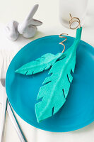 Turquoise felt feathers on blue plate