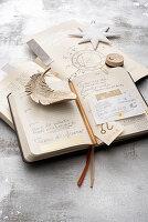 Aufgeschlagener Taschenkalender auf Astrologiebuch mit Deko-Stern