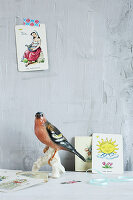 China bird and vintage-style playing cards against grey wall