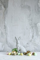 Easter bunny and eggs against grey rendered wall