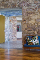 Wooden sofa with blue upholstery and colourful scatter cushion next to open doorway in stone house