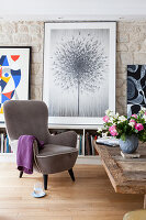 Grey armchair in front of picture of dandelion clock in living room