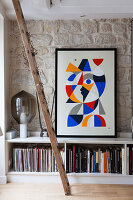 Leaning ladder in front of abstract artwork on low sideboard holding books