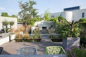Terrasse mit Betonfliesen und Teich