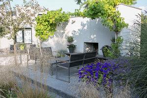 Outdoormöbel auf der Terrasse vor Kamin