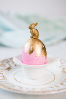 Bunny on top of pink Easter egg with gold leaf