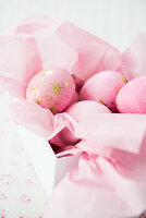 Pink eggs with gold leaf on paper in box