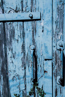 Wooden door with peeling blue paint