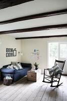 Schaukelstuhl und blaues Sofa im schlichten, ländlichen Wohnzimmer