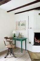 Alter Stuhl am grünen Tisch neben dem offenen Kamin