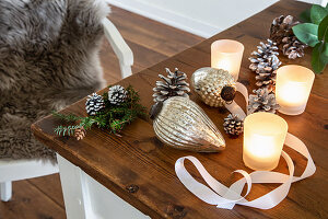 Christmas-tree baubles, pine cones and tealight holders