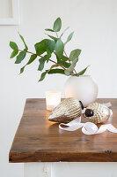 Weihnachtsbaumanhänger, Kugelvase mit Blätterzweigen und Windlicht auf Holztisch