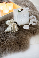 Christmas-tree bauble, gift box and tray of tealights on fur rug