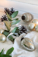 Christmas-tree baubles, pine cones and leafy branches