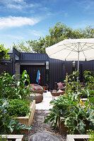 Blick vom Gemüsegarten auf Terrasse mit Outdoormöbeln und Feuerstelle