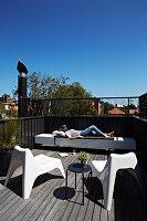 Frau entspannt sich auf Dachterrasse mit Designermöbeln