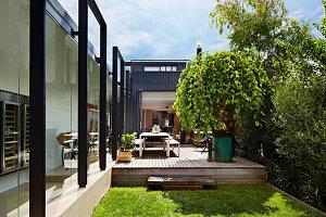 Blick auf Holzterrasse vor Glasfassade