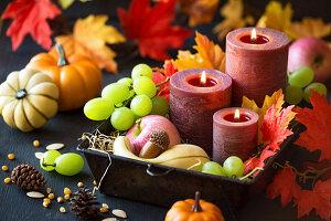 Erntedank-Dekoration mit Kerzen, Herbstfrüchten, Kürbissen und Laublättern