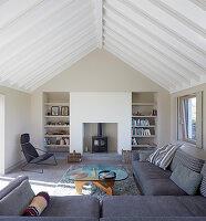 Wohnzimmer mit grauer Sofagarnitur, Coffeetable und Kamin