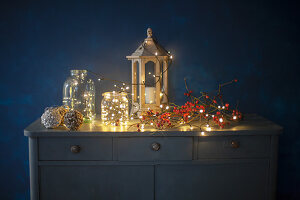 Lantern, glass jars, branch of berries and fairy lights on top of chest of drawers