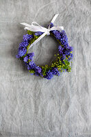 Small wreath of grape hyacinth flowers with white ribbon on grey surface