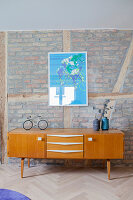 Sideboard below blue poster on brick wall of living room