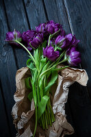 'Purple peony' tulips in brown paper on wooden surface