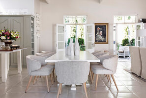White dining table and elegant upholstered chairs in open-plan interior