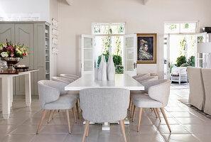 Weißer Esstisch mit eleganten Polsterstühlen in offenem Wohnraum