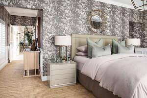 Elegant double bed with bedside cabinets in bedroom with patterned wallpaper