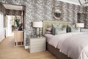 Elegantes Doppelbett mit Nachtkästchen im Schlafzimmer mit Tapete