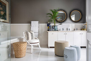 Pale furnishings and dark walls in elegant bathroom
