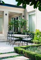 Blick vom Garten auf Terrasse mit Tisch und Stühlen