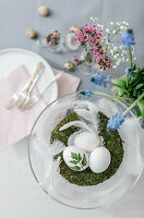 A wreath of moss with Easter eggs and spring flowers in glasses