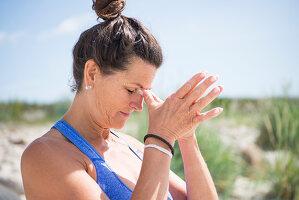 Reife Frau macht Yoga-Übung (Namasta-Geste) am Strand